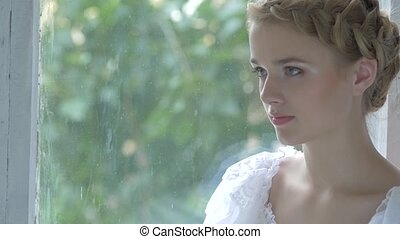 Young blonde girl in white vintage dress smeling flowers, slow motion