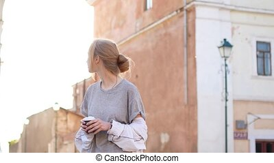 Young blonde girl is wondering down the streets. Cute smile. Summer, sun is shining,t. No people around, female portrait.