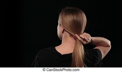 Back view of cute woman with pony tail letting her hair down isolated on black background. Blonde female with amazing long hair fluttering with wind. Slow motion.