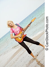 Young blonde girl with guitar on the beach.