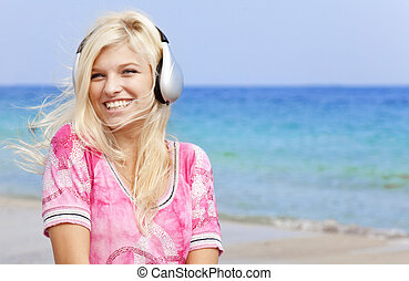 Young blonde girl with headphone on the beach.