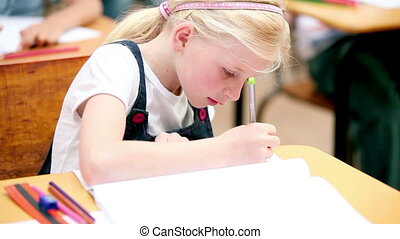 Young blonde girl writing on her notebook