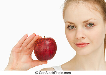 Young blonde-haired woman presenting an apple