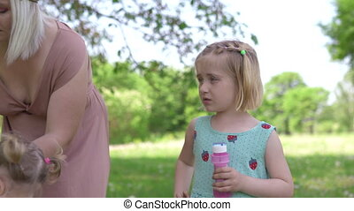 Young blonde hippie mother having quality time with her baby girls at a park blowing soap bubbles - Daughters wear similar dresses with strawberry print - Family values concept