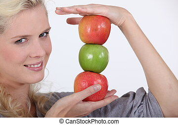 young blonde holding pile of apples