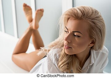 Young blonde in ligerie lying on a window sill - Young...
