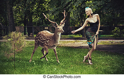 Young blonde lady running with deer