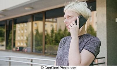 Young Blonde Lady Speaking on the Phone in Town