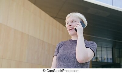 Young Blonde Lady Speaking on the Phone in Town - An...
