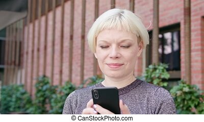 Young Blonde Lady Using a Phone in Town - An attractive...