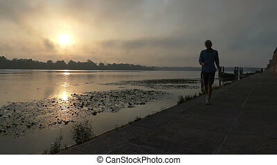 Young Blonde Man Goes Along The Dnipro River Happily at a Sunset in Slo-Mo
