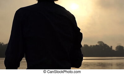 Young Blonde Man Stands on a Picturesque Riverbank at Sunset
