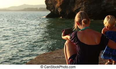 mother makes selfy near daughter against cliff at sunset