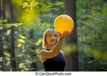 Young blonde pilates trainee holding a yellow ball