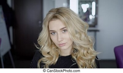 Young blonde posing for the camera. A close shot of a beautiful face photos. Hairdresser made for stylish wave pattern and natural makeup, with which she would go on a date with a guy