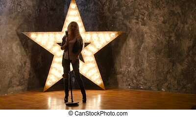Young blonde singer with curly hair, microphone, dances. shining star in the background. slow motion