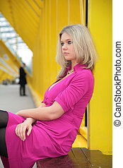 young blonde sits on footbridge
