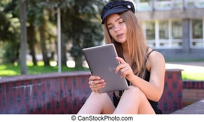 Young blonde sitting on bench working on tablet pc. Female...