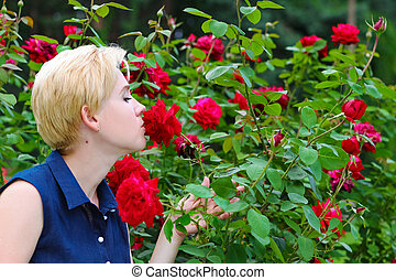 Young blonde sniffs red roses in a garden on a bush.