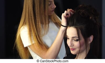 Young blonde stylist girl makes hairstyle to a woman