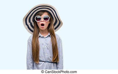 Young blonde toddler wearing hat and sunglasses scared in shock with a surprise face, afraid and excited with fear expression