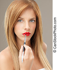 young blonde woman applying red lipstick brush