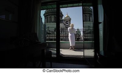 Young blonde woman at balcony