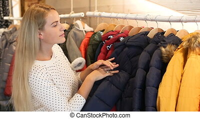 Young blonde woman choosing baby clothes small size in shop