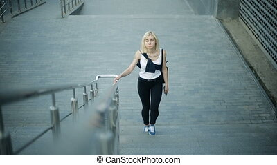 Young blonde woman climbs the stairs in the city. Moves towards the camera and passes by.