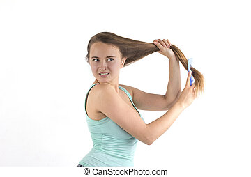 Young blonde woman combing hair
