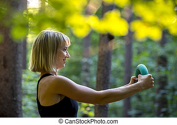 Young blonde woman doing pilates power exercise bending a rubber accessory