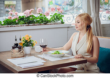 Young blonde woman drinking red wine in an outdoor restaurant