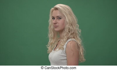 Young blonde woman in a white top is turning to the camera...