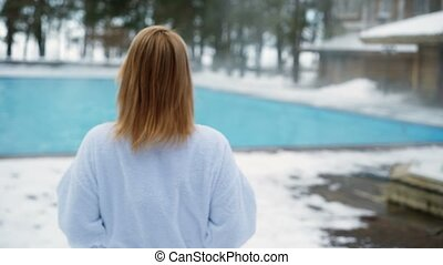 Young blonde woman goes to outdoor swimming pool at winter...