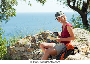 woman hiking - young blonde woman hiking sitting on a rock...