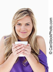 Young blonde woman holding a cup of coffee