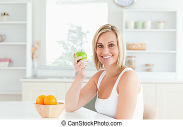 Young blonde woman holding a green apple smiling into the camera in the kitchen