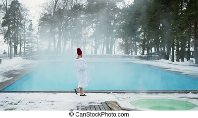 Young blonde woman in bathrobe and red hut near outdoor...