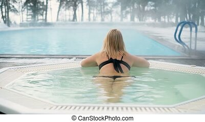 Young blonde woman in bathtub jacuzzi outdoors at winter day