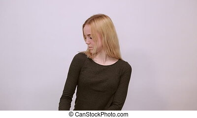 Young Blonde Woman In Black Sweater With Stylish Watch On White Background, Confident Girl Shows Arm Muscles, Demonstrates Biceps. The Concept Of Strong People