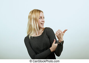 Happy Smiling Attractive Girl Shows Thumb Finger Direction To The Side