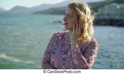 Young blonde woman in dress near sea