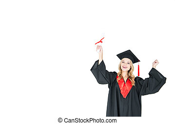 Young blonde woman in graduation gown holding diploma and triumphing on white