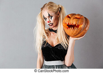 Young blonde woman in halloween clown make-up