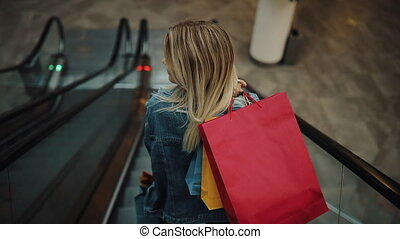 Young blonde woman in jeans jacket goes down on the moving staircases in the shopping mall