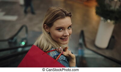 Young blonde woman in jeans jacket smiles going down on the moving staircases in the shopping mall