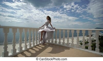 Young blonde woman in lingerie posing at terrace with sea...