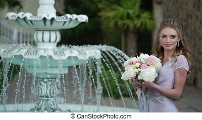 Young blonde woman in lingerie posing with bridal bouquet in...