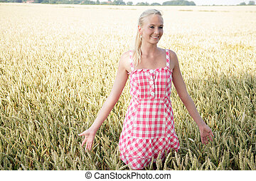 young blonde woman in nature - Young woman walking through a...