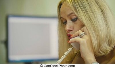 Young Blonde Woman in office talking on phone in front of the computer, close up